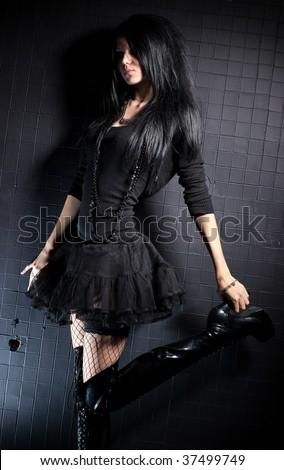 Goth woman fashion. On black wall background. - stock photo