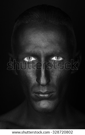 Gothic and Halloween theme: a man with black skin is isolated on a black background in the studio, the Black Death body art - stock photo