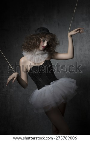 gothic fashion shoot with uncombed brunette wearing like gothic puppet with tutu, bowler hat and clown make-up. - stock photo