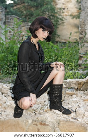 Gothic girl in black clothes in the ruins of the house - stock photo