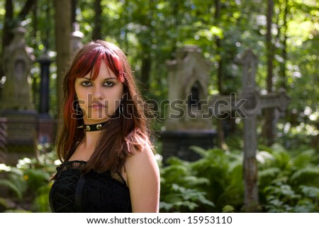 Gothic girl walking through cemetery looking at you - stock photo