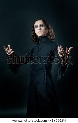 gothic men in black soutane isolated on black - stock photo