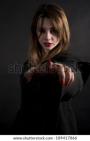 Gothic priestess with finger pointing you - stock photo