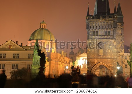 Gothic tower and church domes seen from the Charles bridge in foggy autumn night, Prague, Czech Republic - stock photo