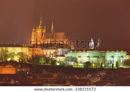Gothic towers of St Vitus Cathedral and Prague castle illuminated in foggy autumn night, Prague, Czech Republic - stock photo