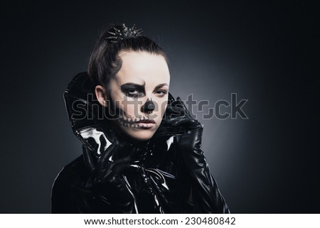 Gothic vamp girl with halloween skull face makeup in shiny black pvc fetish cape dress - stock photo