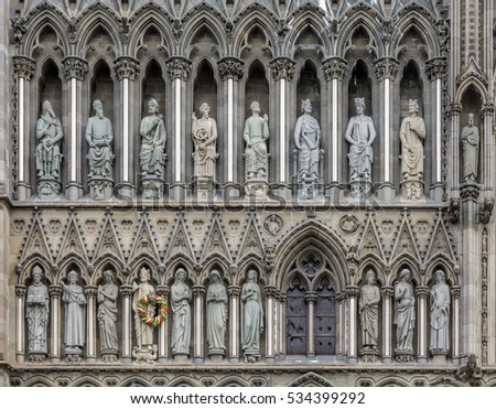 Gothic West Front of Nidaros Cathedral in Trondheim Norway with the statue of Saint Olaf King of Norway decorated with a wreth