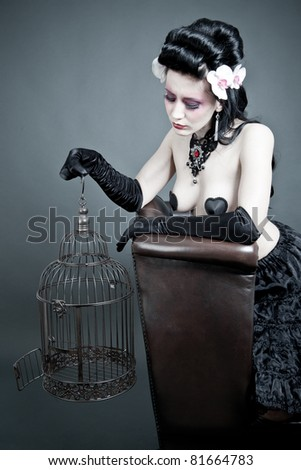 Gothic Woman with a empty birdcage - stock photo