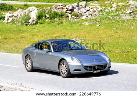 GOTTHARD PASS, SWITZERLAND - AUGUST 5, 2014: Silver supercar Ferrari 612 Scaglietti at the high Alpine mountain road. - stock photo