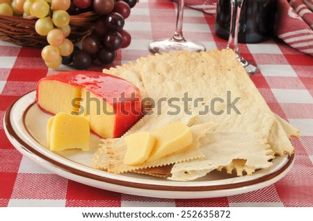 Gouda cheese and gourmet flatbread crackers on a picnic table - stock photo