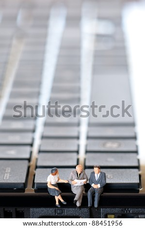 Goup of figurine people sitting on laptop keyboard and reading newspaper - stock photo