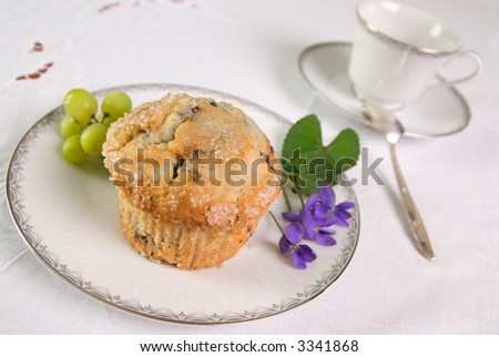Gourmet Blueberry muffin on a silver rimmed plate with grapes and flower garnish with a coffee cup and spoon in the background