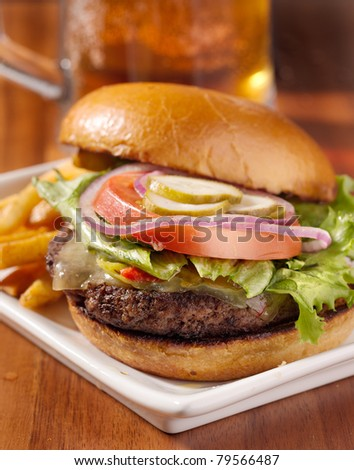 gourmet cheeseburger served open faced with a mug of beer out of focus in the background. - stock photo