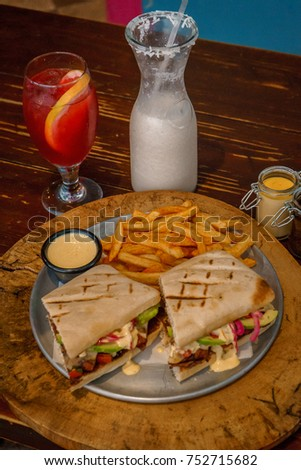 Gourmet ciabata sandwich on wood table, meat and fries, with a drinks on background