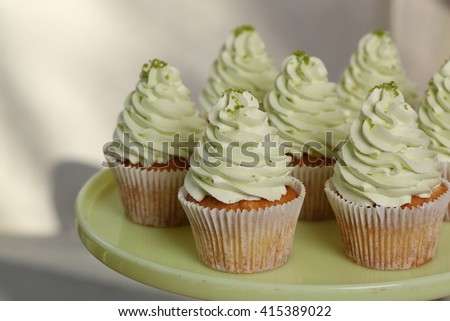 Gourmet cupcakes with green buttercream frosting and sprinkles on the plate. Close up - stock photo
