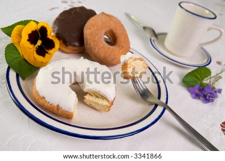Gourmet donuts served on a blue rimmed diner plate garnished with a flower with a cup of coffee