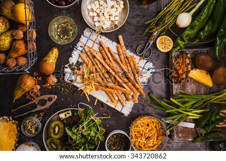 Gourmet food concept. Various Snacks and fruits, veggies table from above. Wholegrain Grissini, feta cheese, fries nuts, tropical fruit sliced, green salad leaves, over dark rustic table.  - stock photo