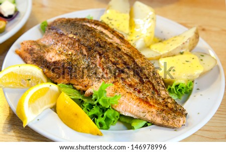 gourmet Grilled Salmon Steak with baked potato and lemon meal - stock photo