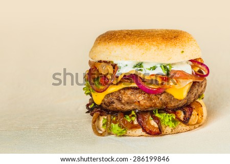 Gourmet Mouth Watering Homemade Hamburger with Cheese, Lettuce, Onions and Tomatoes on a Beige Background with Copy Space. - stock photo