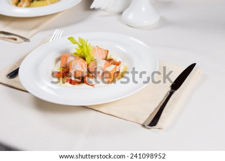Gourmet salmon starter with bite sized portions of delicious grilled fish topped with a savory cream sauce served at table - stock photo