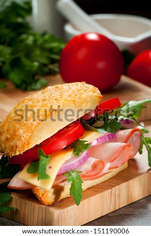 Gourmet sandwich with ham, cheese, fresh tomatoes, salad and a white bread bun, on a wooden cutting board and salad leaves in the background  - stock photo