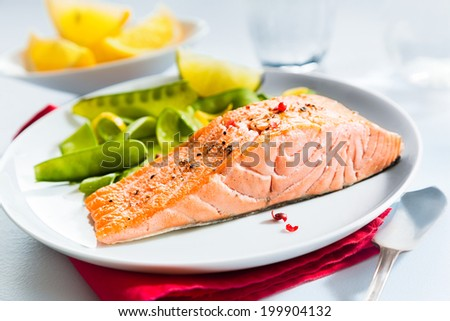 Gourmet seafood meal of grilled salmon steak served with fresh green mangetout peas and lemon wedges for flavoring - stock photo