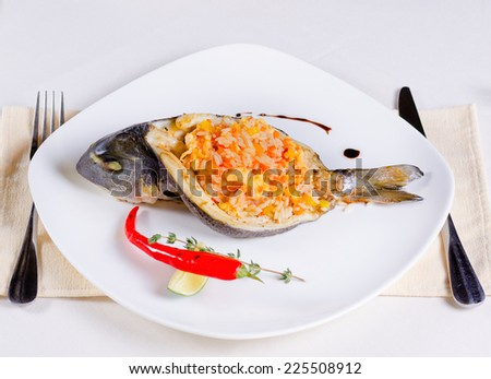 Gourmet Sliced Grilled Fish Stuffed with Tasty Risotto Food, Prepared on White Plate with Lemon and Red Chili Pepper. Served on White Table with Fork and Knife on Sides. - stock photo