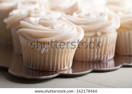 Gourmet strawberry filled cupcakes with white chocolate frosting - side view - stock photo