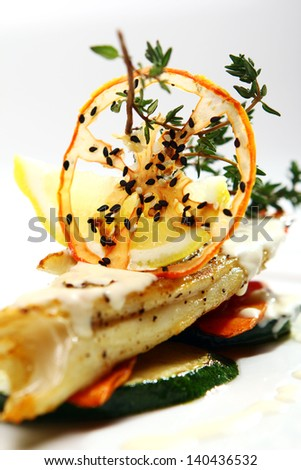 Gourmet style grilled fish with vegetables and green on a plate - stock photo
