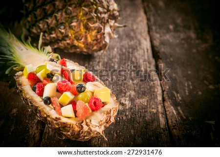 Gourmet Tasty Fresh Fruit Salad in a Pineapple Boat on Top of a Wooden Table, Captured in Close up. - stock photo