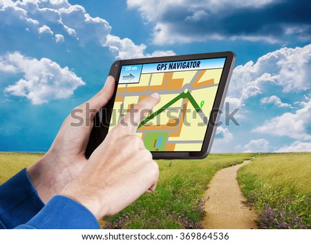 gps hands with digital tablet in landscape and roads - stock photo