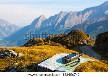GPS navigator and map on Alps mountain background - stock photo