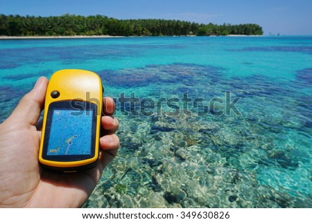 GPS satellite navigator in hand in foreground over blurred sea with a coral reef under water surface and an island at the horizon, natural scene, Caribbean, Panama - stock photo