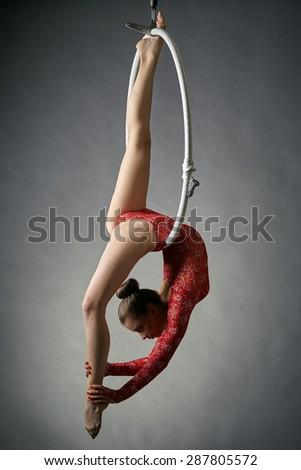 Graceful acrobat performs gymnastic trick on hoop - stock photo