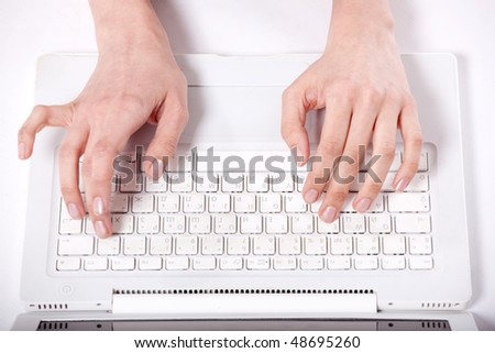 Graceful female hands print the text on the keyboard of a computer