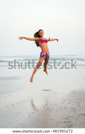 Graceful happy black woman dancing and jumping at the beach. Sporty female having fun and enjoying ocean freedom.