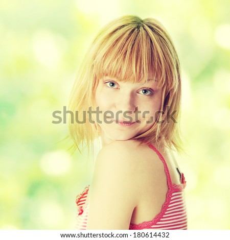 Graceful young blond woman in underwear posing on abstract green background - stock photo