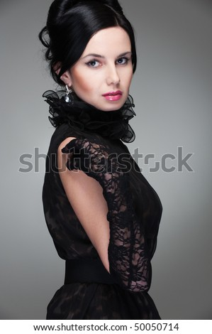 graceful young woman in black dress posing against grey background - stock photo