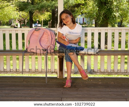 Grade school girl doing homeowrk outside on school grounds on a sunny day - stock photo
