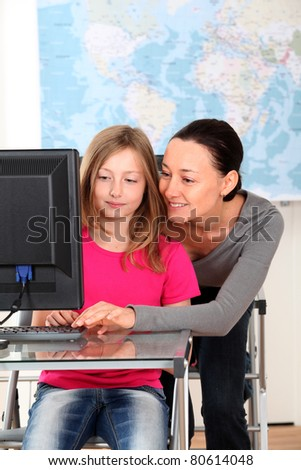 Grade-school girl in class with teacher - stock photo