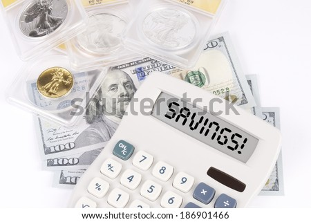 Graded Coins and Currency with a Calculator that spells out SAVINGS! on the display - stock photo