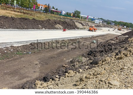 Grader is working on gravel leveling for the new road on construction site. - stock photo