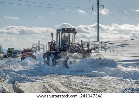 Grader removes snow from road after storm - stock photo