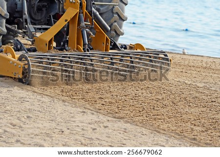 Grader Sifting Sand On Public Beach