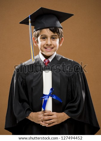 Graduate boy with mortarboard holding his diploma and smiling - stock photo