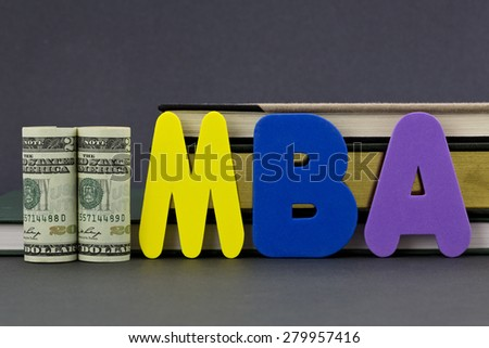Graduate degree MBA letters with dollar currency in front of books on gray background.  Advance degree is a education business investment in critical skills.   - stock photo