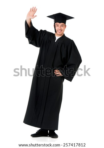 Graduate guy student in mantle greets with his hand, isolated on white background