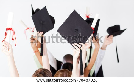 graduate holding graduation caps and certificate