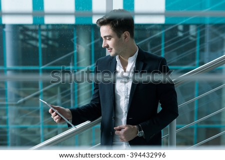 Graduate in suit with tablet standing in modern building