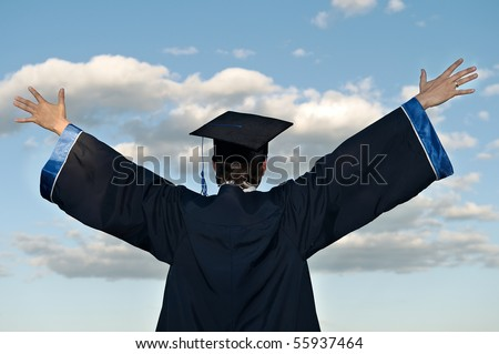 graduate student in cloak with open arms over blue sky (rear view) - stock photo